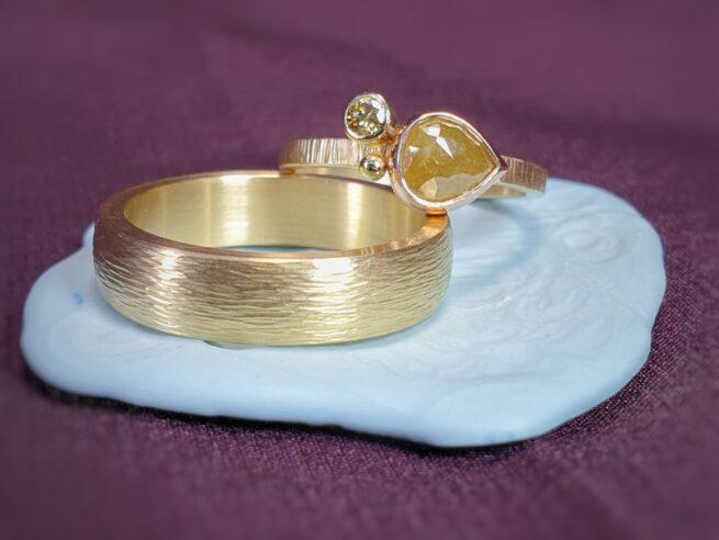 Handgemaakte trouwringen met spitse hamerslag en natural diamant. Ontwerp van goudsmid Oogst in Amsterdam.