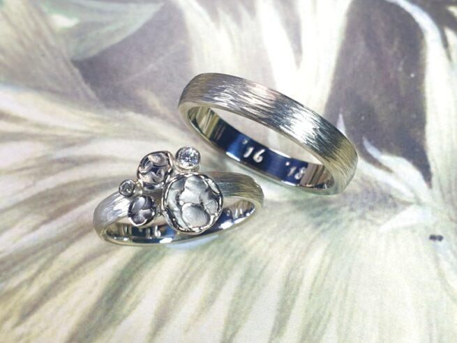 Witgouden trouwringen met hamerslag cirkel bloemen en diamant. Maatwerk trouwringen uit het Oogst atelier.