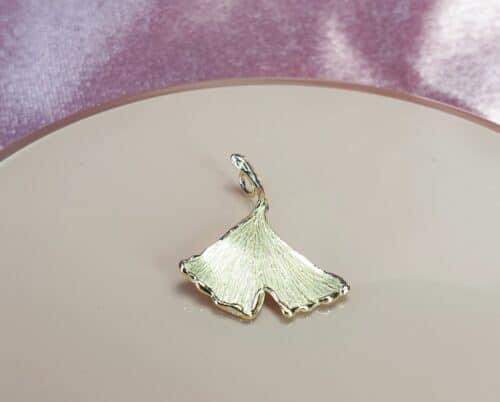 Geelgouden hanger Ginkgo blad aan een verfijnd ankerschakel collier. Handgemaakt door Oogst Sieraden.