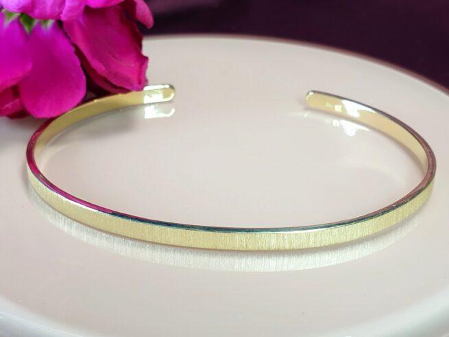 Geelgouden klemarmband 'Eenvoud'. Geboortesieraad voor Robin. Maatwerk uit het Oogst atelier