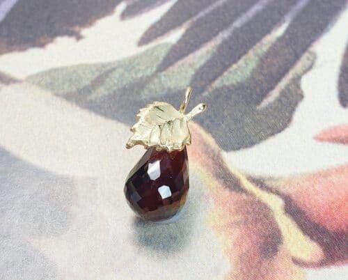 Geboortesieraad hanger. Geelgouden Berkenblad met granaat briolet. Ontwerp van Oogst Goudsmeden in Amsterdam