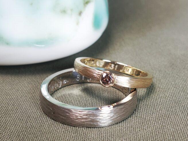 Trouwringen Ritme. Witgouden ring en roodgouden ring met bruine diamant met spitse hamerslag. Maatwerk van Oogst Goudsmeden