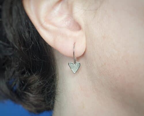 Wiltgouden oorbellen Hartjes met krul . Ontwerp van Oogst Sieraden in Amsterdam