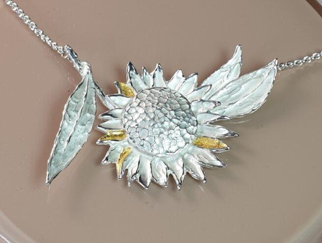 Assieraad. Zilveren Zonnebloem collier met bladgoud details. Maatwerk van Oogst Goudsmeden in Amsterdam
